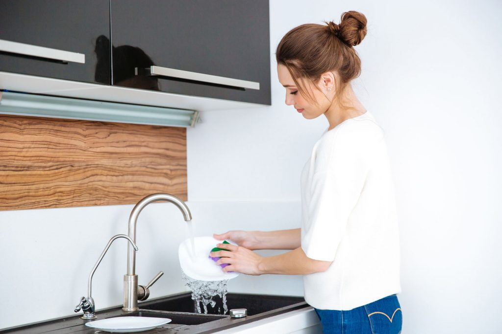 Woman washing dishes with Salt-Free Conditioned Water